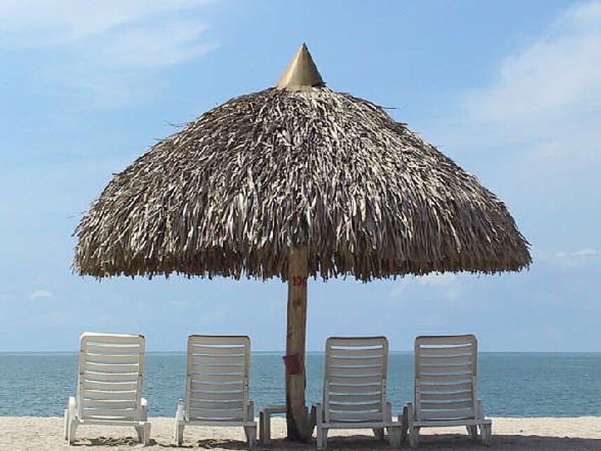 Vista de Playa Blanca lanzarote. Sombrilla y tumbonas sobre la arena y el mar de fondo